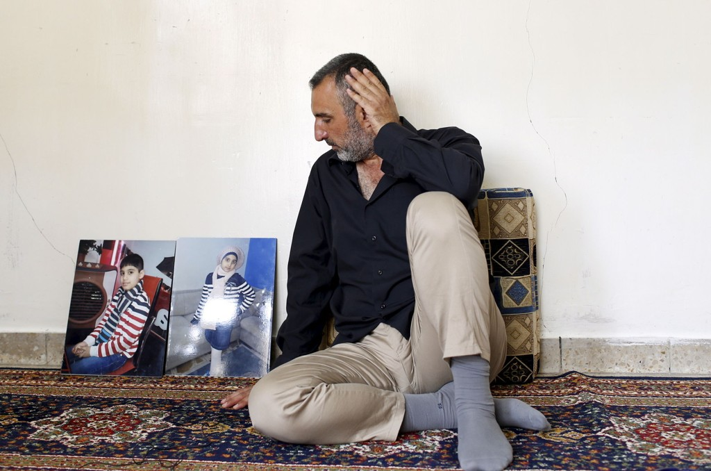 Ahmed Hadi Jawwad, whose children drowned while trying to reach Greece, sits next to pictures of them during an interview with Reuters in Baghdad. Abdullah Kurdi, the father of drowned Syrian toddler Aylan Kurdi, was working with smugglers and driving the flimsy boat that capsized trying to reach Greece, other passengers on board said, in an account that disputes the version he gave last week.