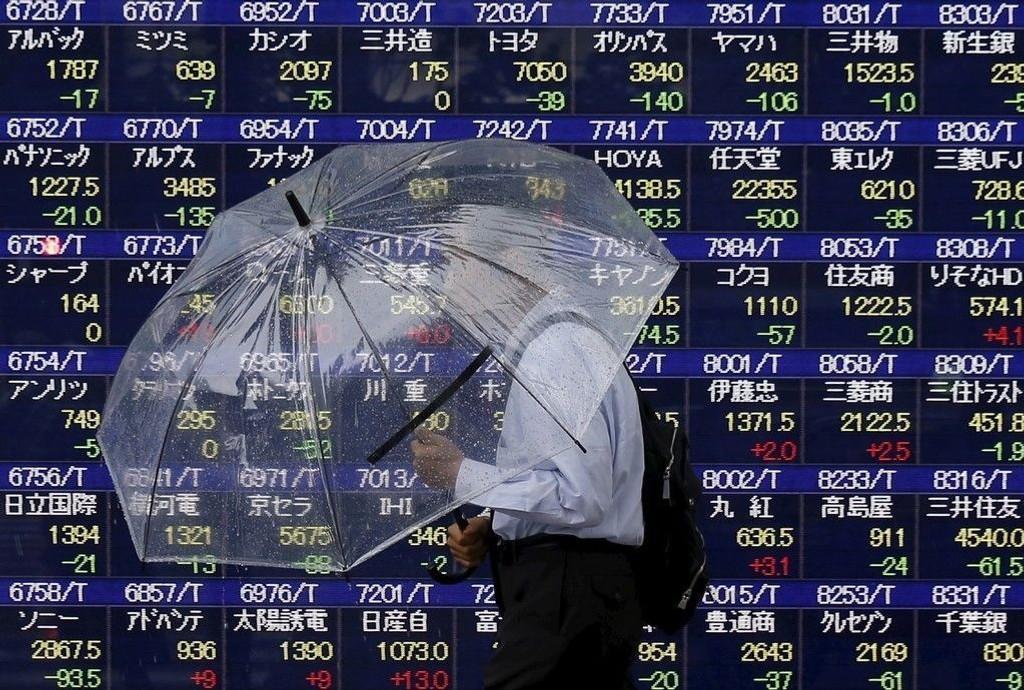 En mann med paraply går forbi en tavle med børskurser i Tokyo. Mandag åpnet markedet med nedgang.