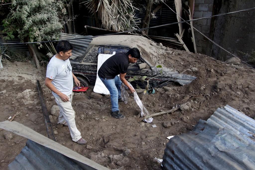 Lokale innbyggere graver etter eiendeler etter at et stort jordskred begravde opp mot 90 hus i en landsby utenfor Guatemalas hovedstad fredag.