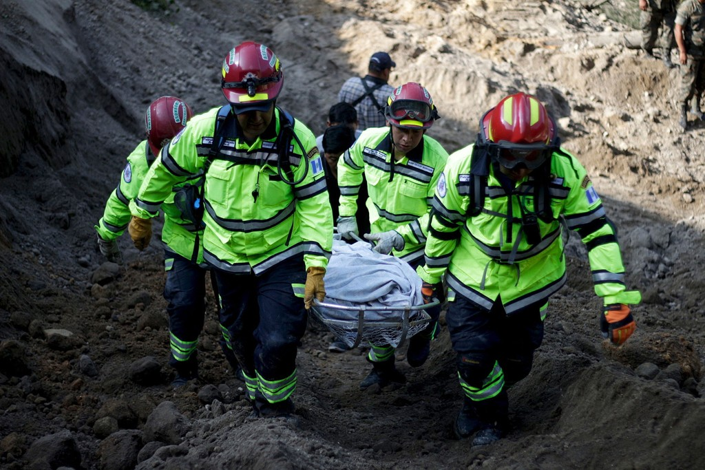 Rescue team members carry the body of a landslide victim in Santa Catarina Pinula, on the outskirts of Guatemala City.