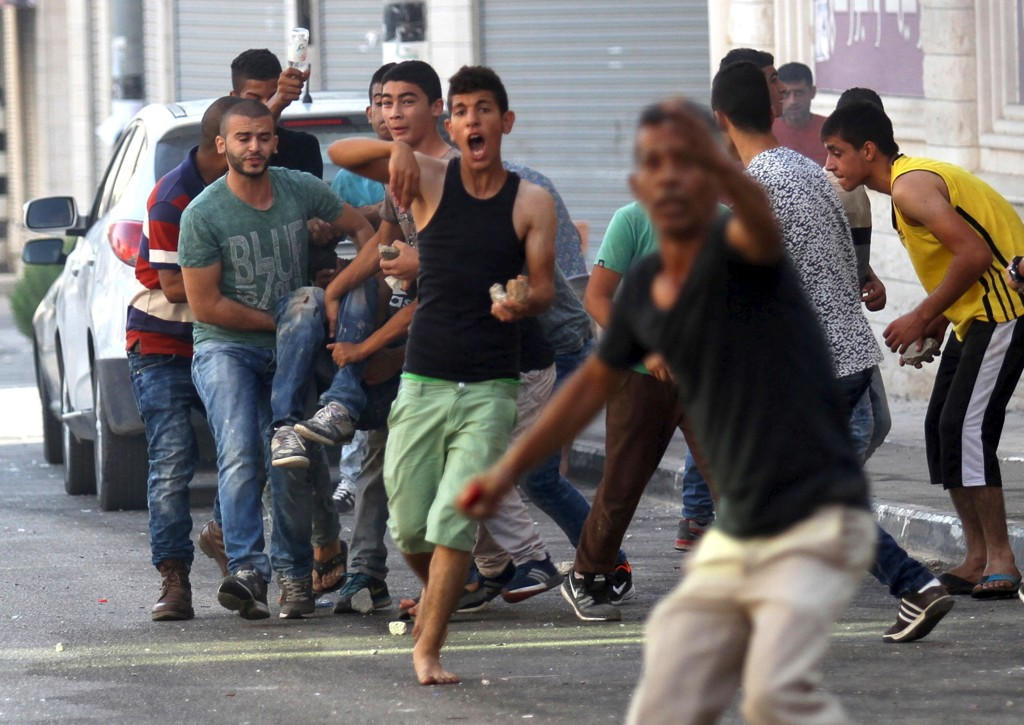 RAIDET: Palestinske ungdommer bærer på en såret kamerat undre sammenstøt med israelske soldater som søndag raidet flyktningleiren Jenin på den okkuperte Vestbredden. Foto: Abed Omar Qusini / Reuters / NTB scanpix