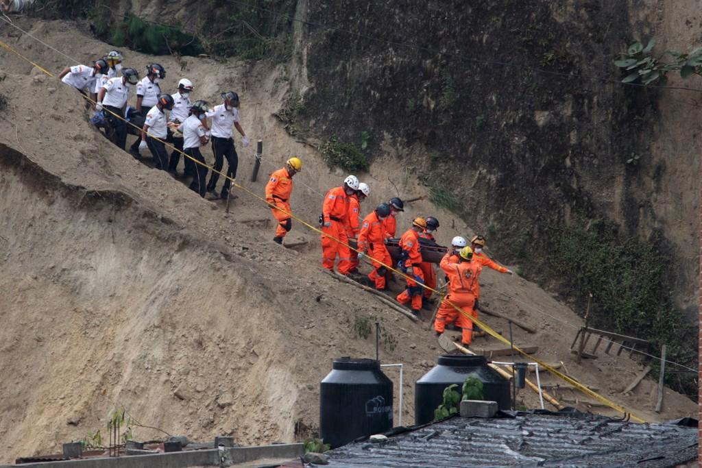 HENTER UT OFRENE: Redningsarbeidere bærer ut døde etter jordskredet i Santa Catarina Pinula utenfor Guatemala City.
