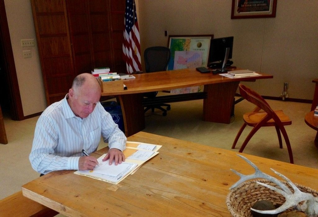 Californias guvernør Jerry Brown signerer et dokument på sitt kontor.