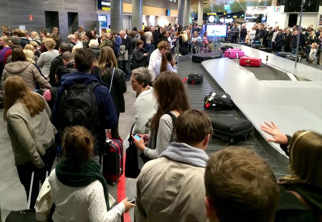Folk i kø i terminalbygningen på Trondheim lufthavn Værnes søndag kveld, etter at flyplassen ble stengt på grunn av tåke.