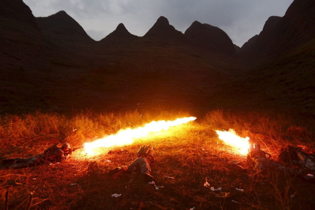 Kinesiske spesialstyrker brukte flammekaster for å tvinge terrormistenkte ut av en fjellhule tidligere denne måneden. Bidet viser kinesiske styrker som benytter flammekaster til å sprenge landminer på grensen til Vietnam.