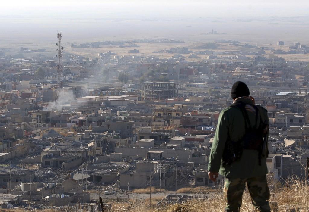 Et medlem av den kurdiske peshmerga-militsen ser utover Sinjar, som nylig ble erobret tilbake fra ekstremistgruppa IS. Flere massegraver er siden blitt funnet på stedet.