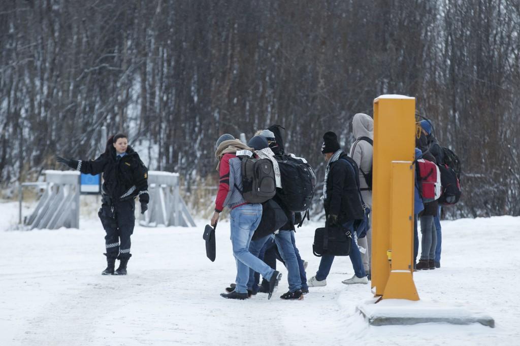 En norsk politikvinne sammen en gruppe asylsøkere på Storskog grensestasjon på den norsk-russiske grensen.