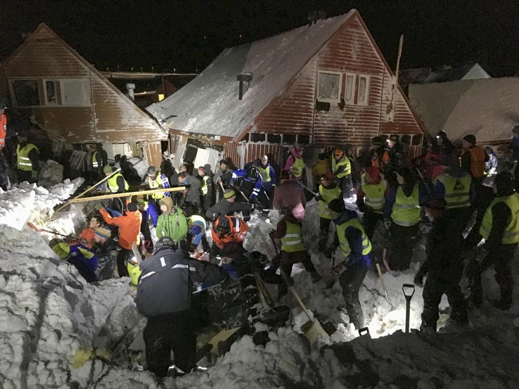 JOBBER PÅ SPRENG: Hjelpemannskaper jobber i området der et snøskredet har truffet flere hus i Longyearbyen. Folk bes melde seg med spader.