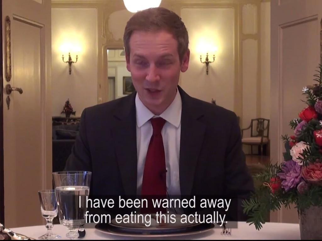 En av de ambassadeansatte prøver seg på rakfisk.