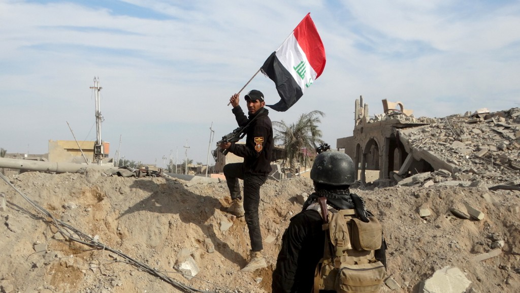 Et medlem av de irakiske sikkerhetsstyrkene holder et irakisk flagg i byen Ramadi.