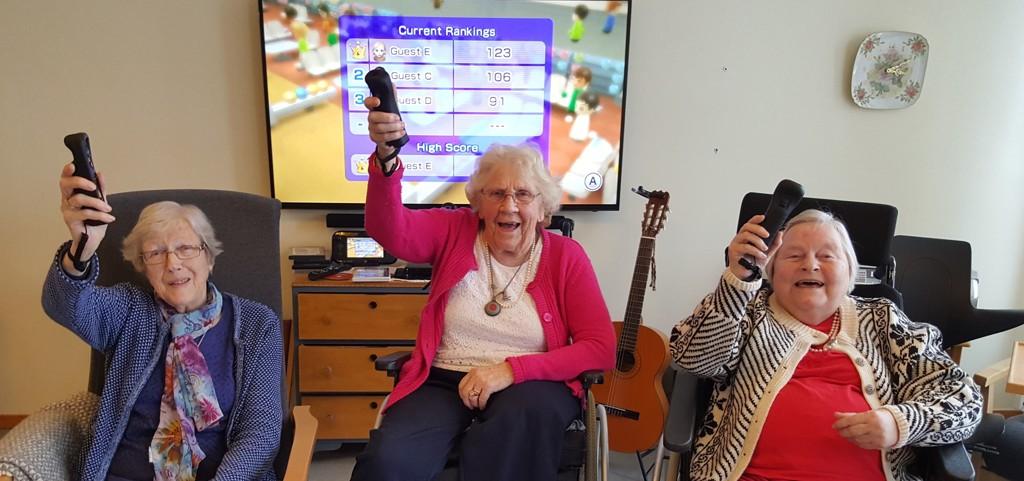IVRIGE DELTAKERE: Karin Kinn, Elsa Solberg og Aud Grønsleth er i full gang med TV-spill. I bakgrunn ses poenginndelingen så langt.
