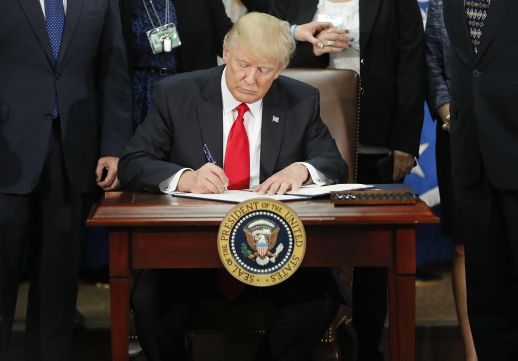 GYVER LØS PÅ JOBBEN: Donald Trump signerer en presidentordre. Det har blitt mange av dem den første uka.