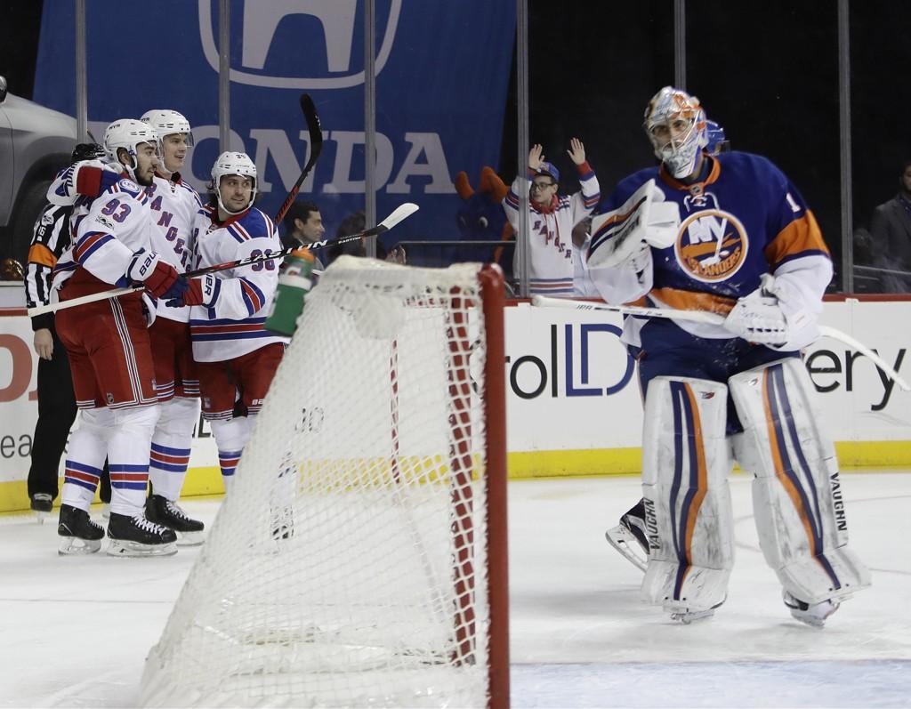 FEIRET: New York Rangers' Nick Holden, Mats Zuccarello og Mika Zibanejad feirer første mål og ledelse i kampen mot New York Islanders. Islanders' målvakt Thomas Greiss til høyre.