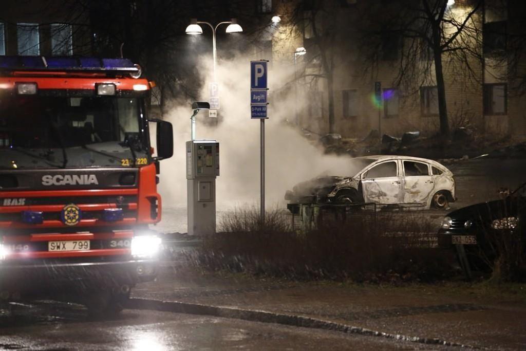 Brannvesenet slukker en av bilene som ble satt i brann i Rinkeby i Stockholm mandag kveld.
