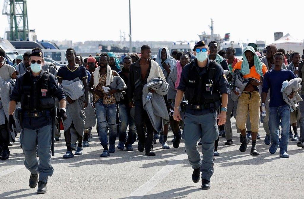 Migranter blir eskortert av italiensk politi etter å ha ankommet i Sicilia i oktober. Arkivfoto.