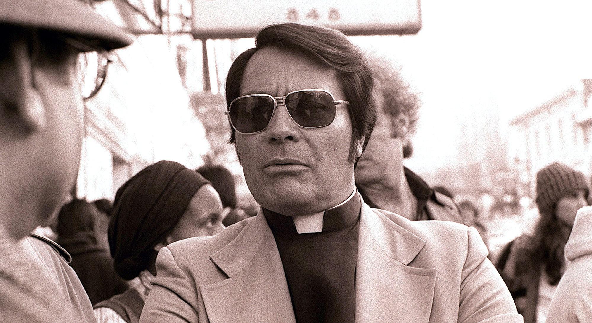 Pastor Jim Jones under en protest foran International Hotel i San Francisco i 1977. Året etter skal han forvandle kolonien i Jonestown til en massegrav av barn, kvinner og menn.