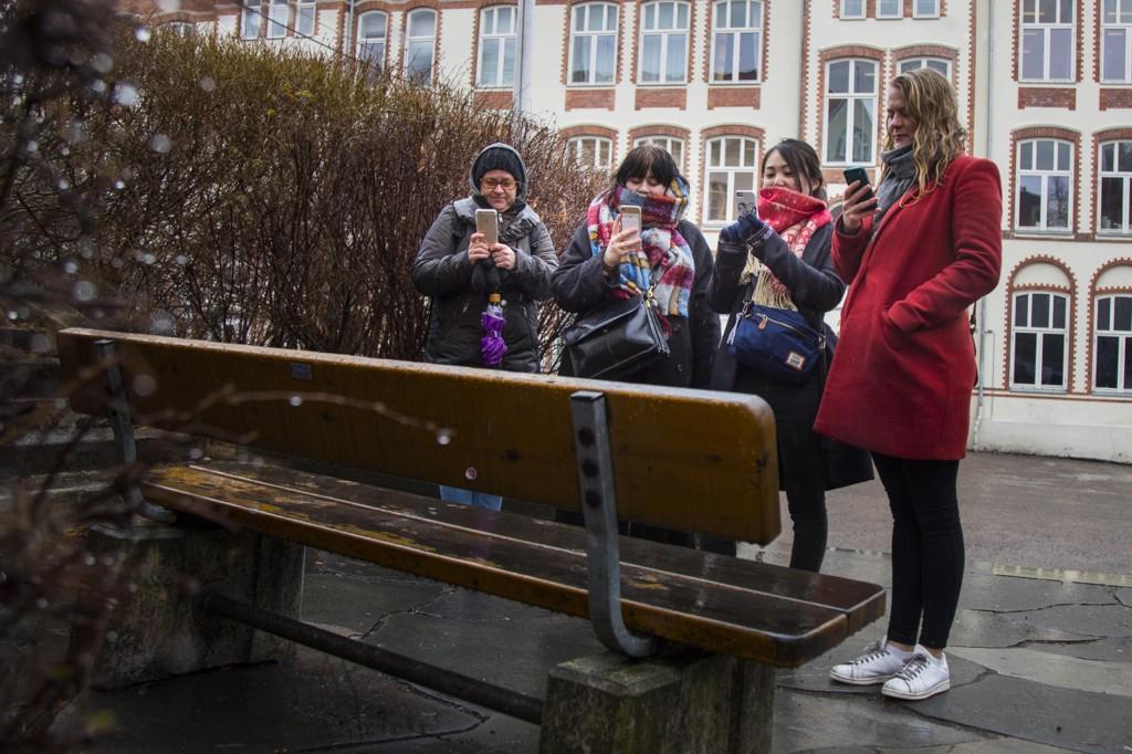 SKAM guide Nina Søraa (tv) og turister fra Japan og Danmark tar mobilbilder av den ikoniske benken på Hartvig Nissen skole, fra SKAM sesong tre der Isaac og Even finner hverandre.
