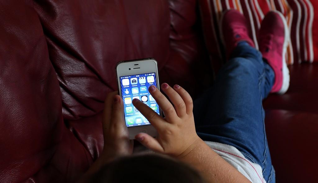 ET BARN bruker smarttelefon. Illustrasjonsfoto.