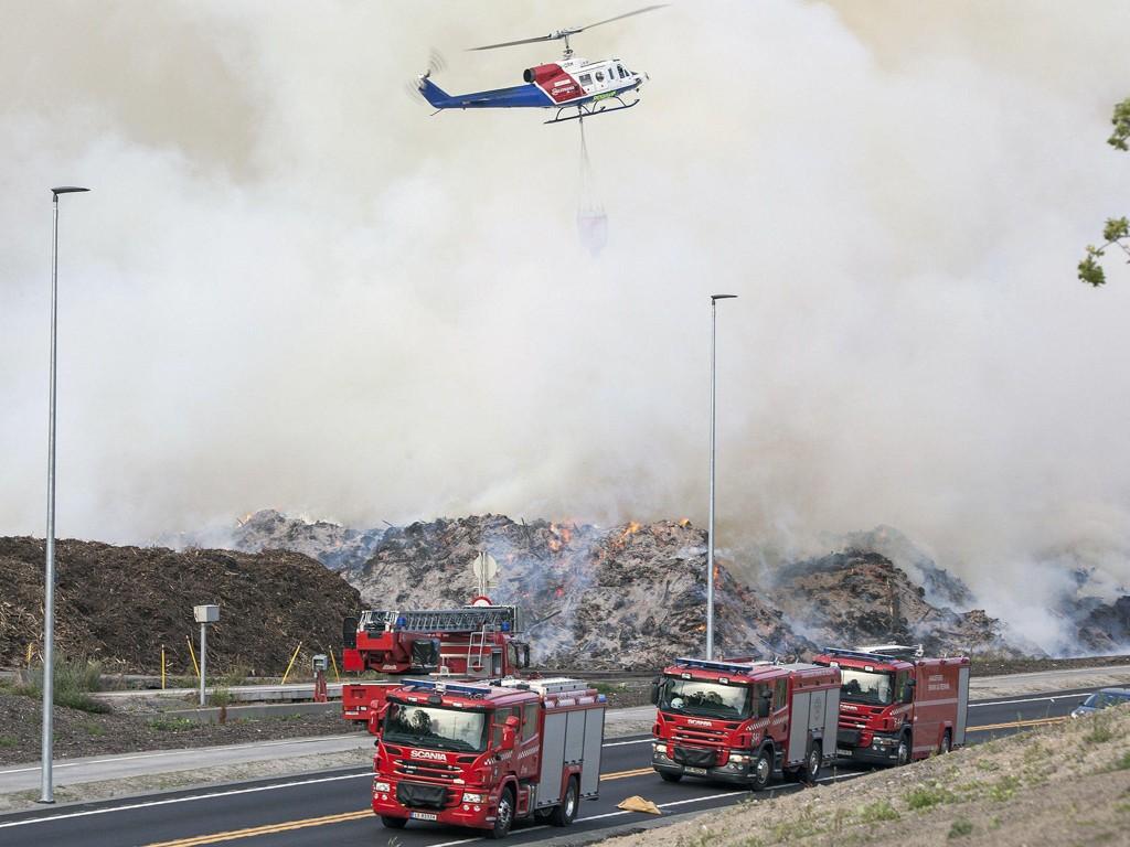 Brannvesenet setter inn helikopter i slokkingen av en omfattende ulmebrann i et barkanlegg på Sky i Larvik lørdag. Sterk røykutvikling truer både naboer og trafikk.
