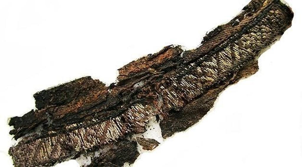 Bildet viser et vevd silkebånd fra en grav fra vikingtiden i Sverige.