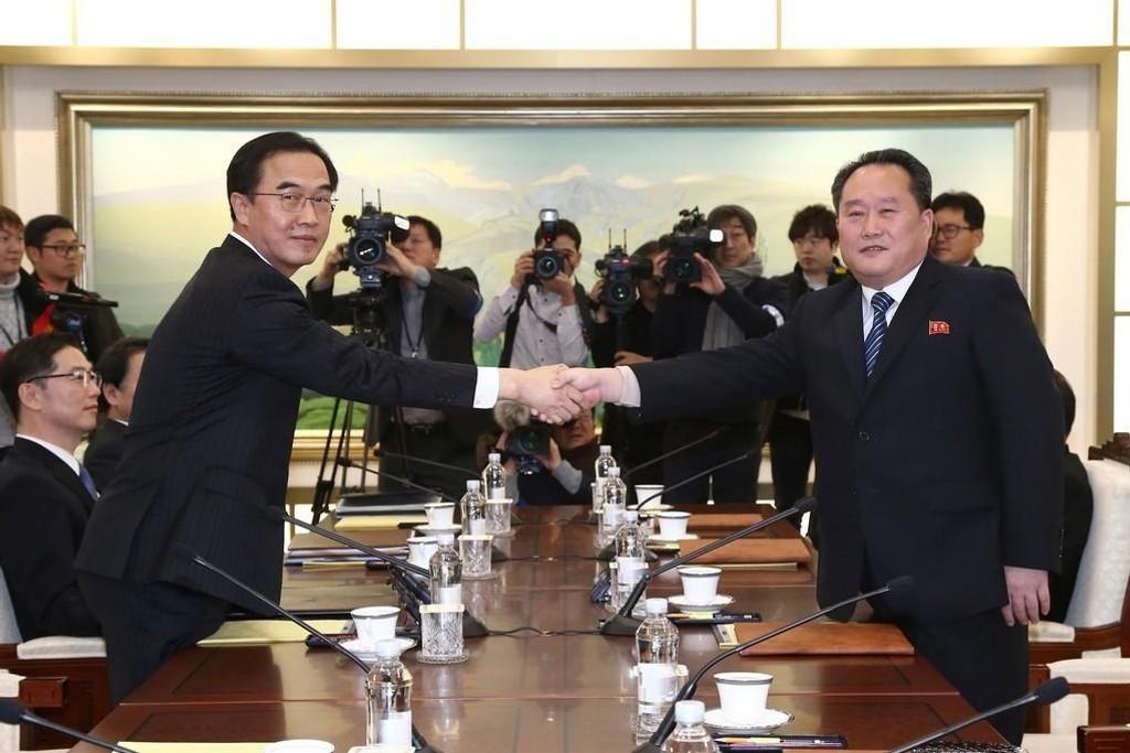 Den sørkoreanske gjenforeningsministeren Cho Myoung-gyon (t.v.) tar sin nordkoreanske motpart Ri Son-gwon i hånden under det første møtet mellom de to landene på to år.