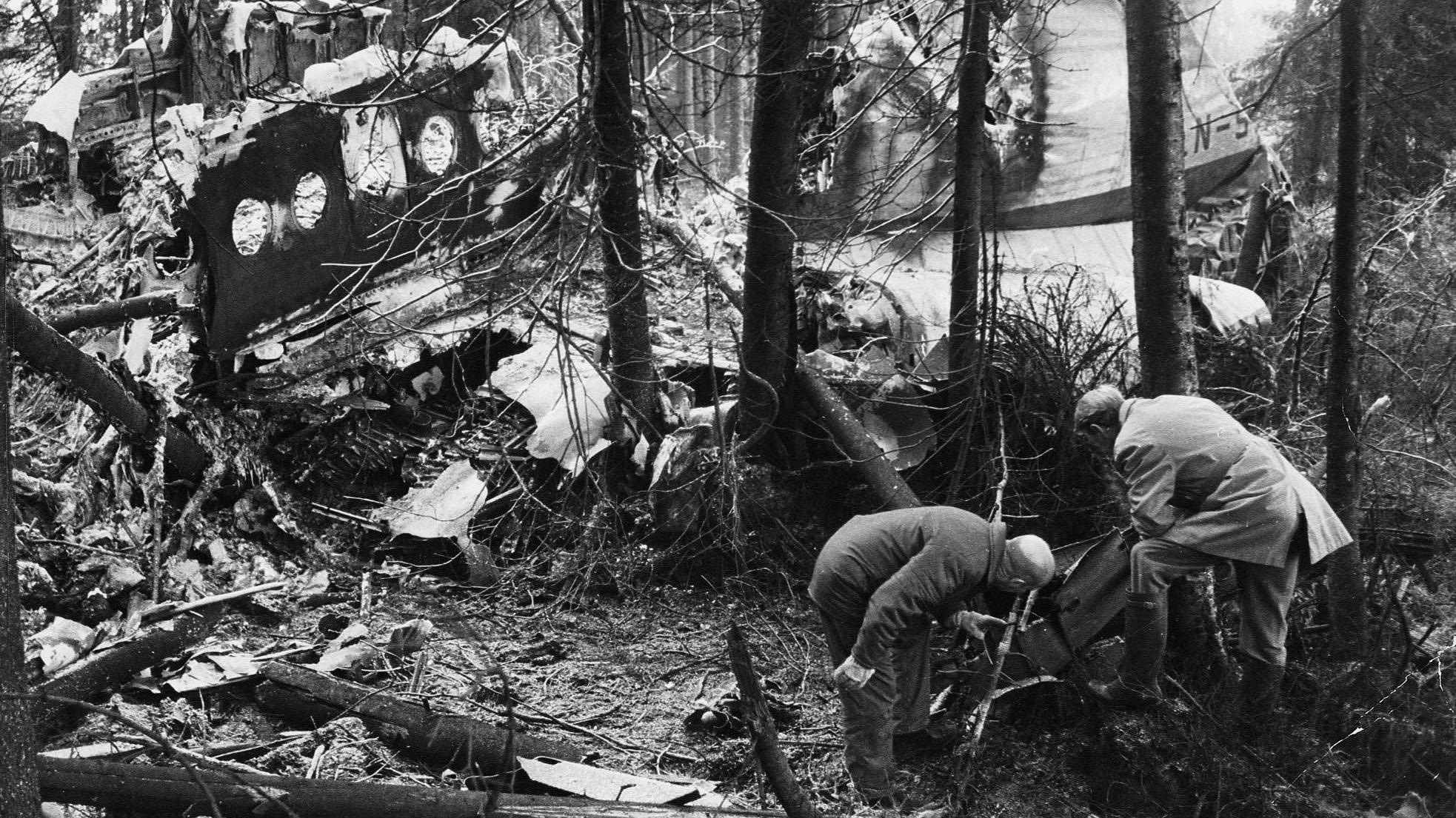 VRAKET: Teknikere fra havarikommisjonen undersøker vrakrestene. I bakgrunnen sees alleen som flyet brøytet gjennom skogen før det traff bakken.