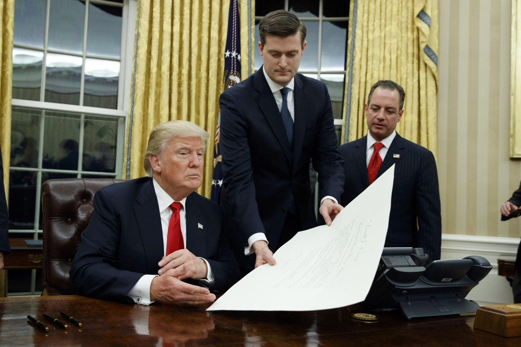I BETRODD STILLING: Rob Porter leverer president Donald Trump et dokument for signering.