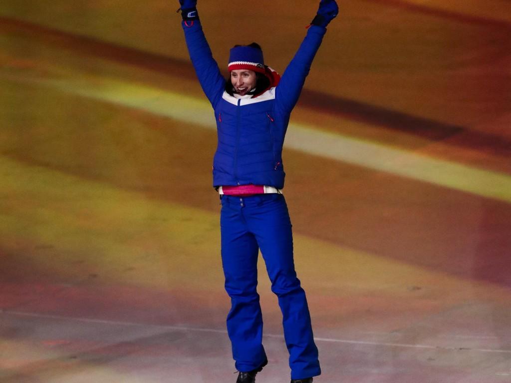 HOPPENDE GLAD: Marit Bjørgen feiret gullet på 30 kilometeren med et seiershopp, under medaljeseremonien. Skidronningen forlater Pyeongchang med med fem medaljer, to gull, et sølv og to bronsemedaljer.