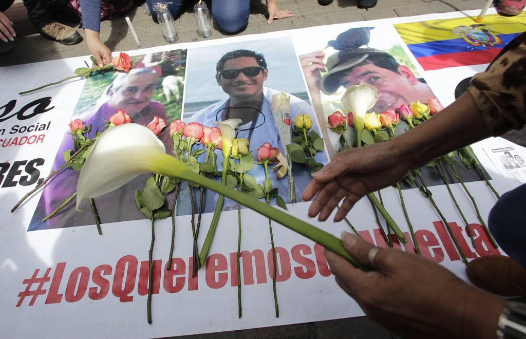 Sørgende ecuadorianere legger ned blomster på bilder av de tre pressefolkene som ble drept i Colombia av en utbrytergruppe fra FARC-geriljaen. Foto: AP / NTB scanpix