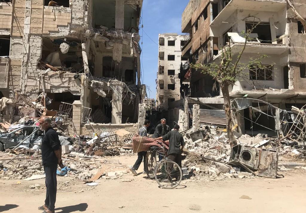 Syrere foran ødelagte bygninger i Douma i Syria mandag. Foto: AP/NTB scanpix
