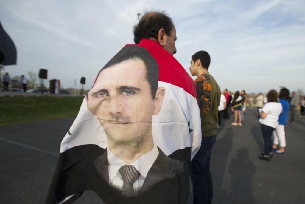 En mann innhyllet i et flagg med bilde av Bashar al-Assad under en markering i Allentown i Pennsylvania i USA. Styrker som støtter den syriske presidenten, skal ha vært i kamp med opprørere som er blitt trent av norske soldater ved en av USAs militærbaser i Syria. Illustrasjonsfoto: AP/NTB scanpix