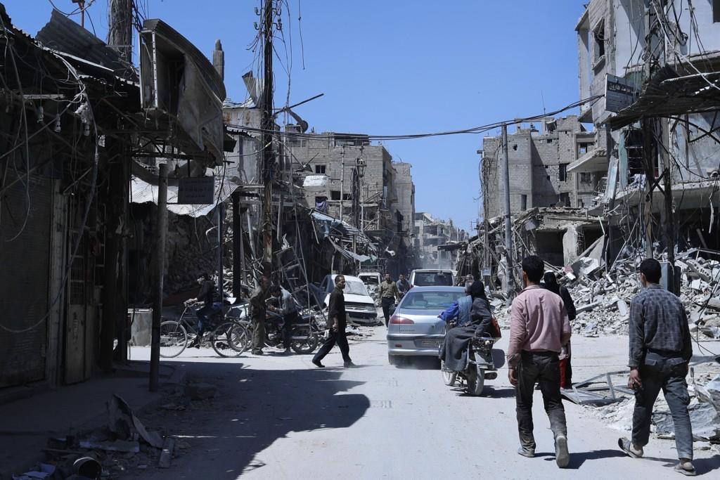 Folk tar seg gjennom gatene blant ruinene i Douma, stedet der Vesten mener det syriske regimet brukte kjemiske våpen mot sivile i byen. Foto: Hassan Ammar / AP / NTB scanpix