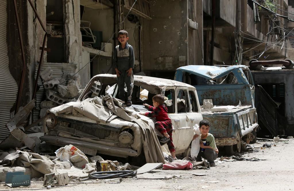 Syriske gutter leker på en ødelagt bil i byen Douma i Syria.