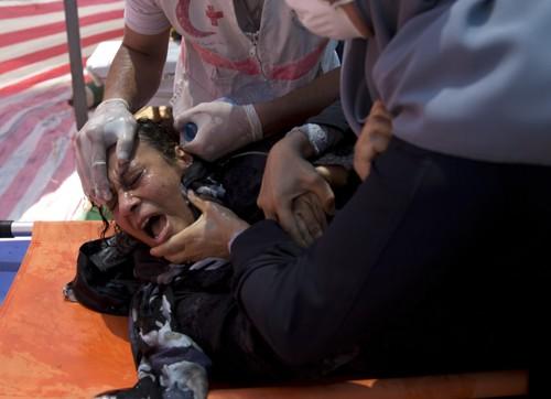 Helsearbeidere behandler en palestinsk kvinne som ble rammet av israelsk tåregass under mandagens demonstrasjon på Gazastripen.
