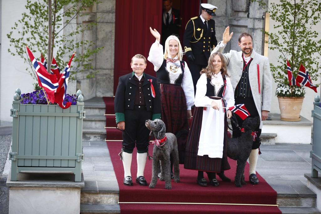 Kronprinsfamilien hilser barnetoget på Skaugum 17. mai (kronprinsesse Mette-Marit, kronprins Haakon, prinsesse Ingrid Alexandra og prins Sverre Magnus).