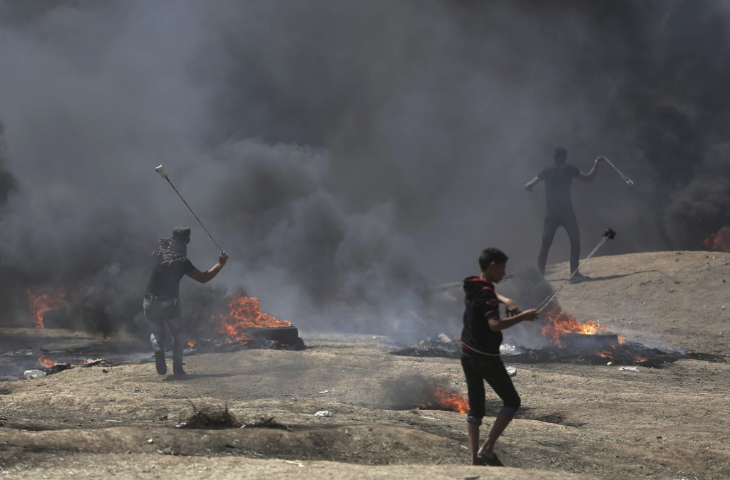 Steinkastende palestinere under demonstrasjonene på Gazastripen mandag, da rundt 60 mennesker ble skutt og drept av israelske soldater. Mange hundre ble såret. Foto: Khalil Hamra / AP / NTB scanpix