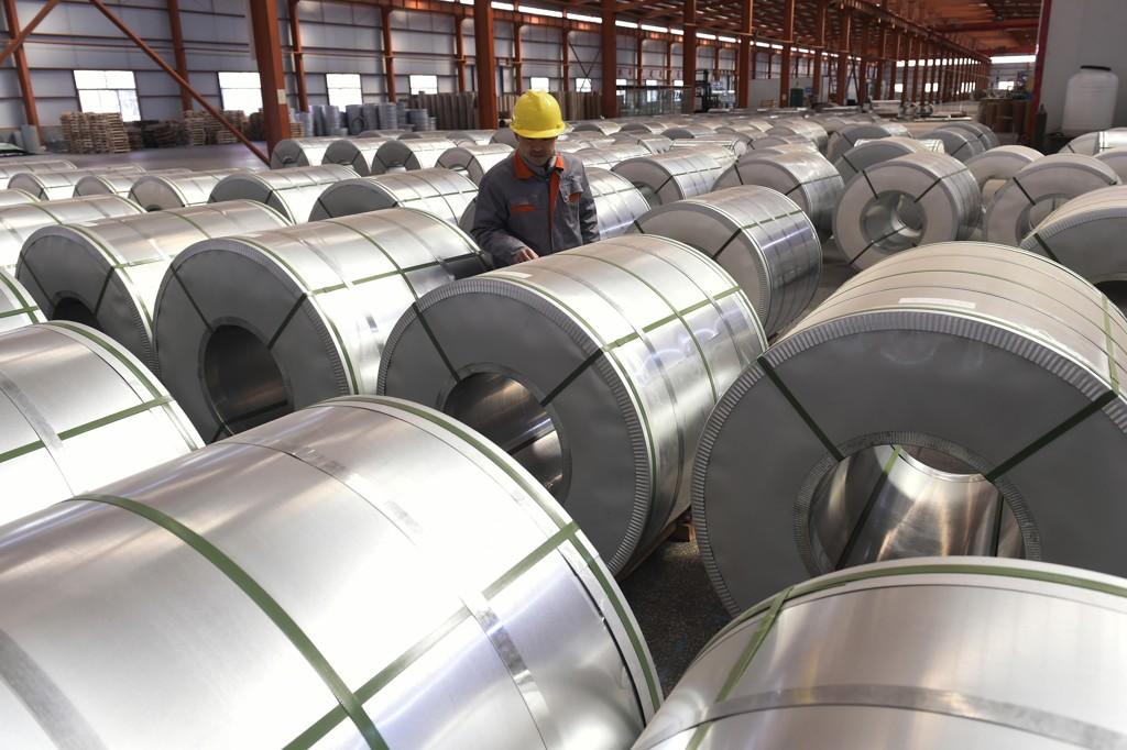 En arbeider inspiserer en forsendelse aluminium i Zouping øst i Kina. Foto: AP / NTB scanpix
