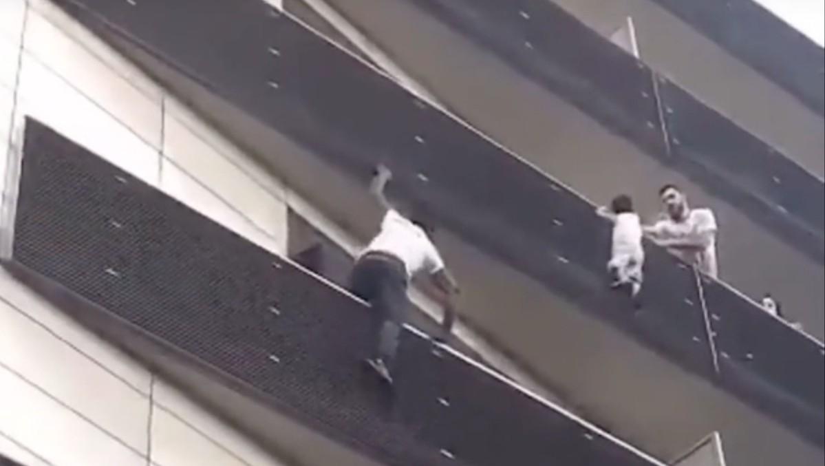 HELT: Mamadou Gassama klatrer opp på utsiden av bygningen for å redde den fire år gamle gutten som henger fra rettverket på utsiden av verandaen.