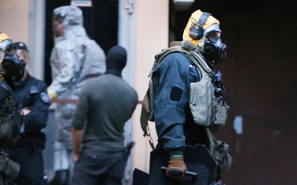 Politifolk i beskyttelsesdrakter under ransakingen av 29-åringens leilighet tirsdag. Foto: AP/NTB scanpix