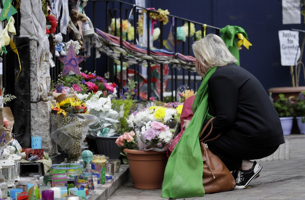 En kvinne kikker på blomster og lys til minne om ofrene for Grenfell-brannen ved en kirke i Notting Hill i London torsdag. Foto: AP/NTB scanpix