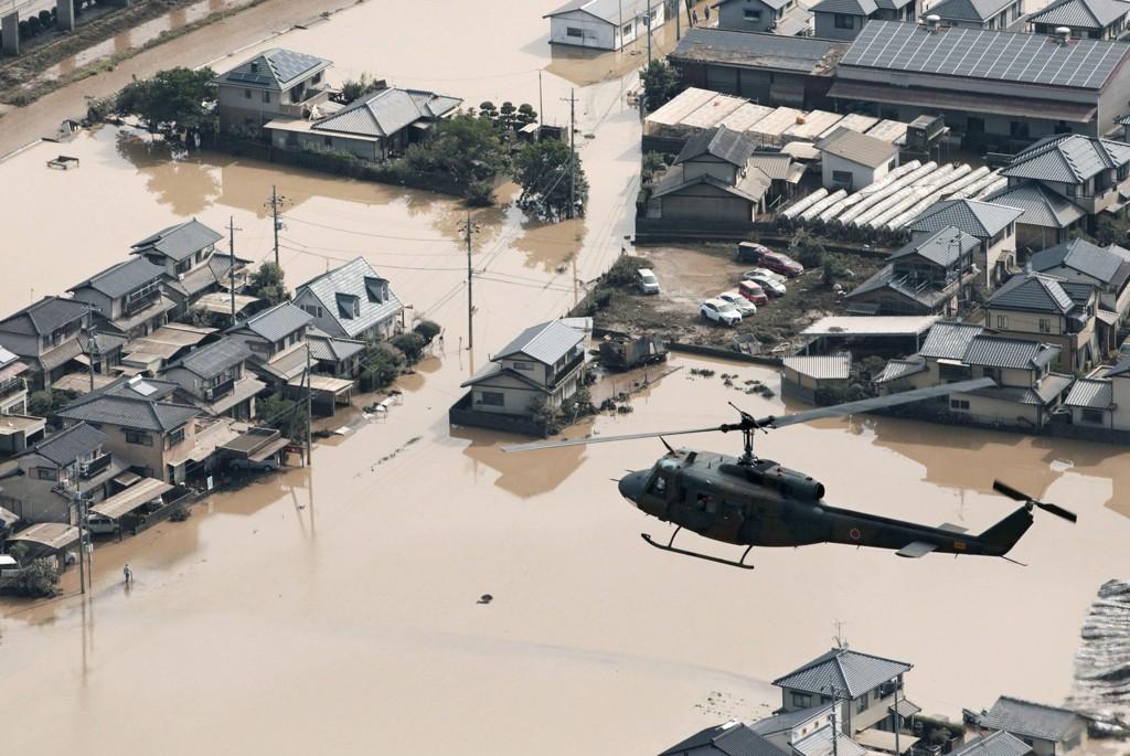 Helikoptre er sentrale i søket etter de titalls savnede sørvest i Japan. Foto: Kyodo News via AP / NTB scanpix