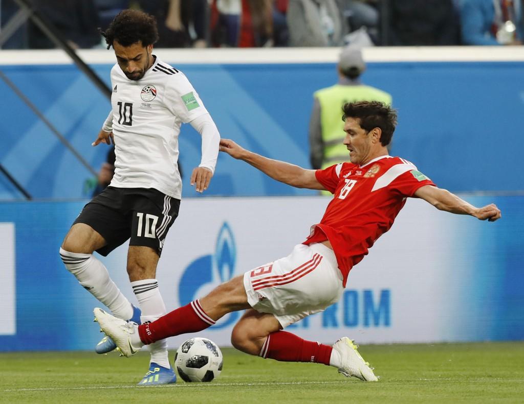 Jurij Zjirkov, som her prøver å takle Mohamed Salah i VM-kampen mot Egypt, gir seg på Russlands landslag etter VM på hjemmebane. Foto: Efrem Lukatskij, AP / NTB scanpix