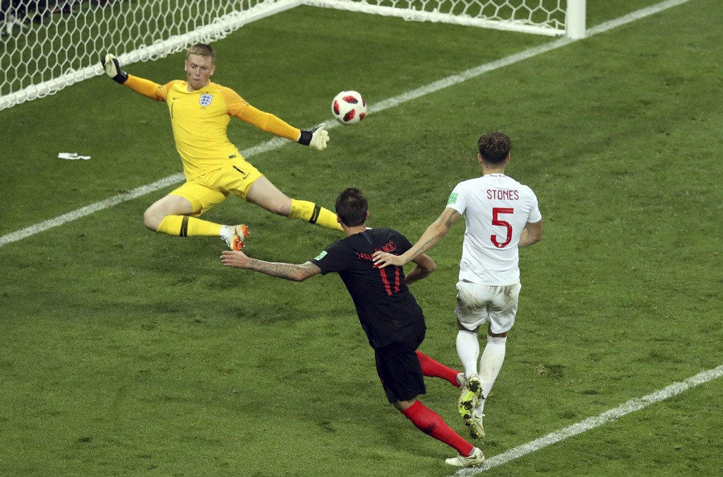 Mario Mandzukic scorer Kroatias vinnermål i VM-semifinalen mot England. Keeper Jordan Pickford og stopper John Stones kan intet gjøre. Foto: Thanassis Stavrakis, AP / NTB scanpix