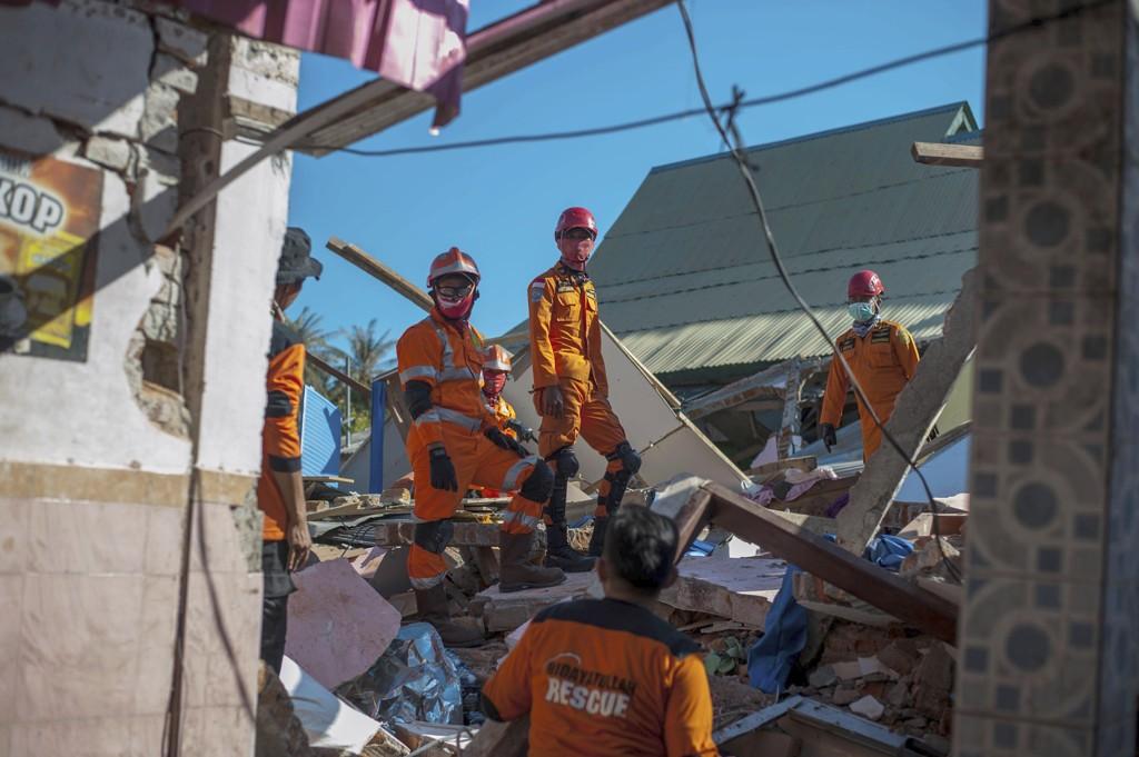 Redningsarbeidere gjennomsøker fortsatt ruiner av hus som raste sammen under søndagens jordskjelv på øya Lombok i Indonesia, og antallet omkomne fortsetter å stige. Foto: AP / NTB scanpix