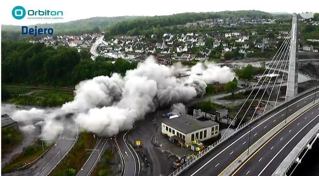 STØVSKY: Slik så det ut da den gamle E18-brua i Larvik ble sprengt ned fredag. Den nye E18-brua ses til høyre på bildet.