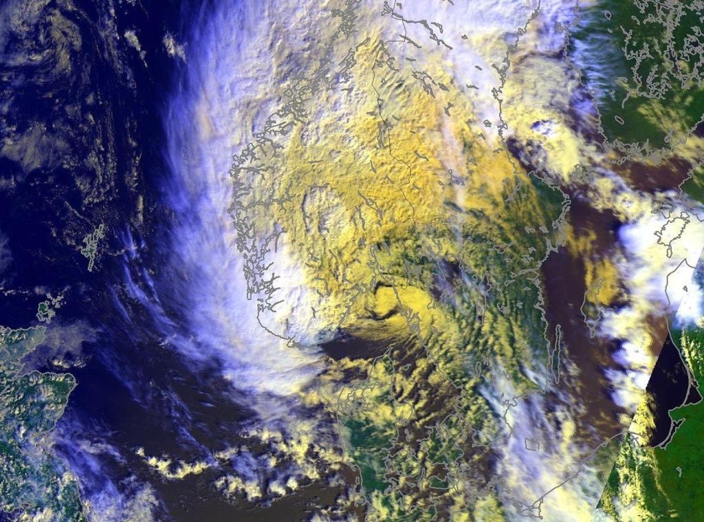 LAVTRYKKETS SENTRUM: Klokka 13 fredag presenterte Meteorologisk institutt dette satellittbildet av uværet som beveger seg inn mot Sør-Norge. Skyene danner en tydelig spiralform rundt det som er lavtrykkets sentrum like ved land.