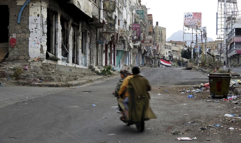 Menn på vei gjennom utbombede Taiz i Jemen, et av eksemplene på hvordan sivilbefolkningen lider i kjølvannet av sammenstøtene mellom koalisjonen og opprørerne i krigen som har herjet landet i tre år. Foto: AP / NTB scanpix