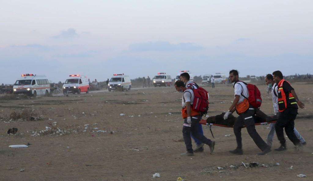 Redningsmannskap evakuerer en såret ungdom fra området ved det israelske grensegjerdet i Khan Younis sør på Gazastripen. Foto: Adel Hana / AP / NTB scanpix