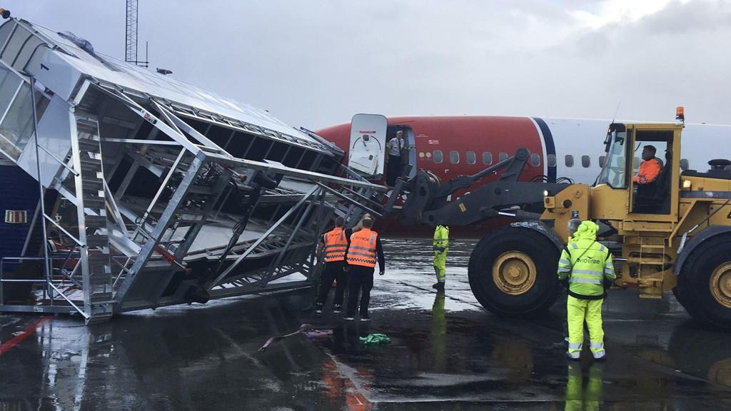 En gangbro på Evenes flyplass ble søndag ettermiddag tatt av et vindkast, noe som førte til at flydøren ble skadd og at evakueringssklien ble utløst. Foto: Pål B. Nygaard / NTB scanpix