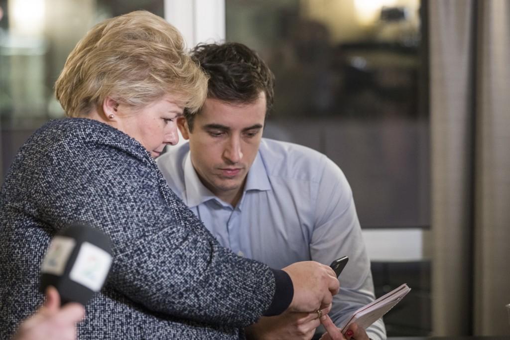 Statsminister og Høyre-leder Erna Solberg ser på mobiltelefonen til Høyres pressesjef Peder W. Egseth. Foto: Håkon Mosvold Larsen / NTB scanpix